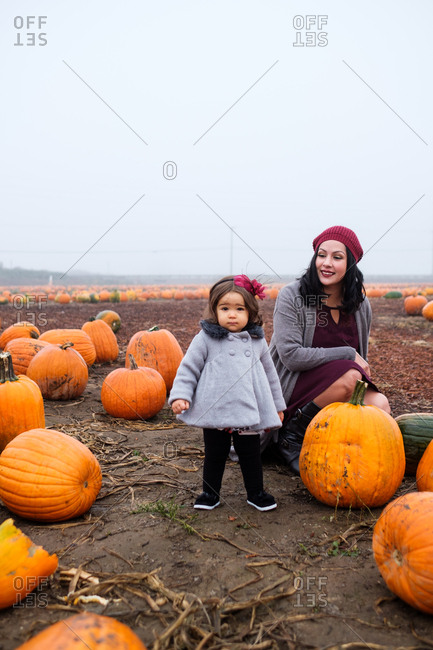 Mother and daughter standing in a pumpkin patch