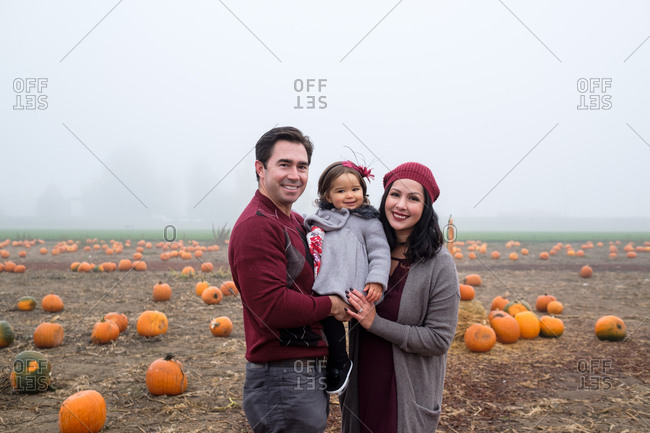 Family posing in a pumpkin patch