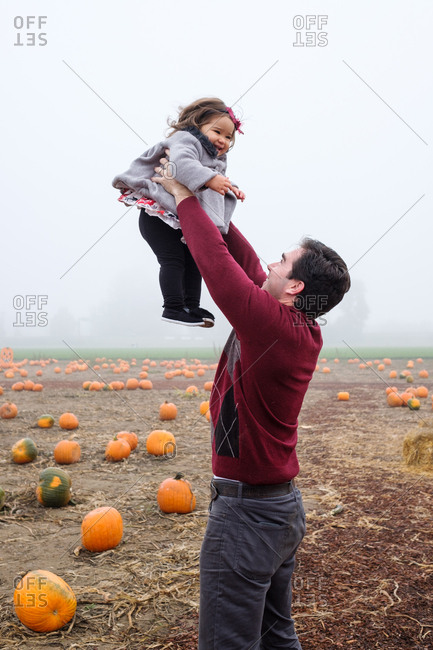 Dad tossing daughter in the air at a pumpkin patch