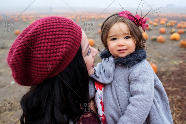 Mother holding daughter in a pumpkin patch