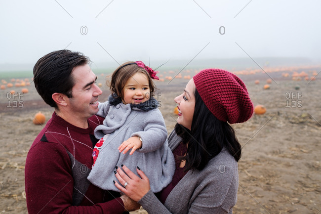 Parents holding daughter at a pumpkin patch