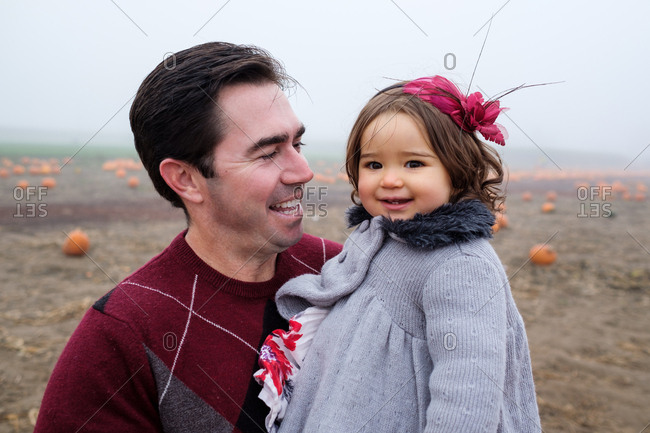 Father holding daughter at pumpkin patch