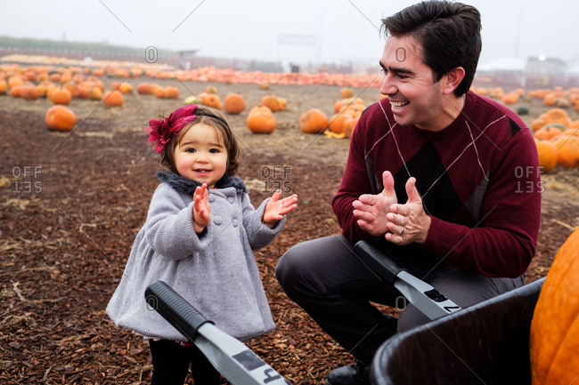 Father and daughter clapping and laughing at a pumpkin patch