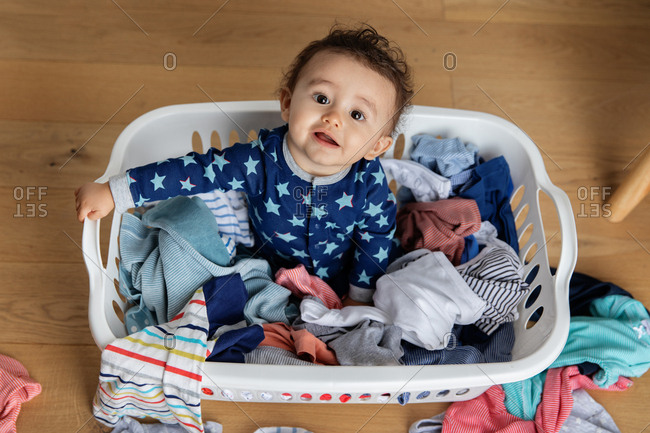 Overhead view of cute toddler sitting in a laundry basket