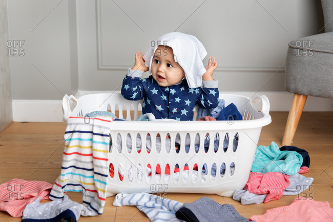 Cute baby sitting in a laundry basket with onesie on his head