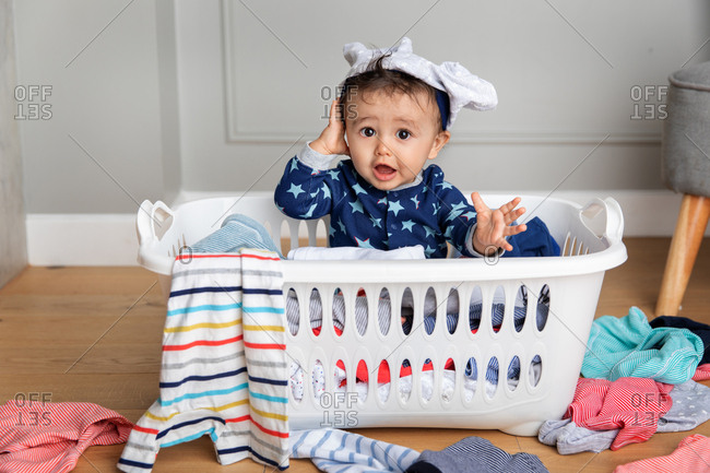 Cute baby sitting in a laundry basket