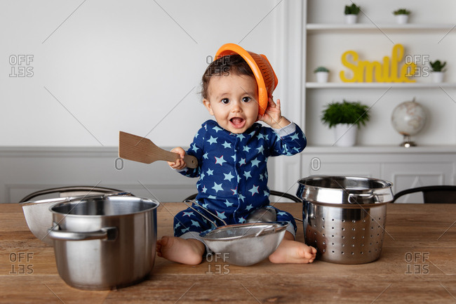 Toddler playing drums with pots and pans