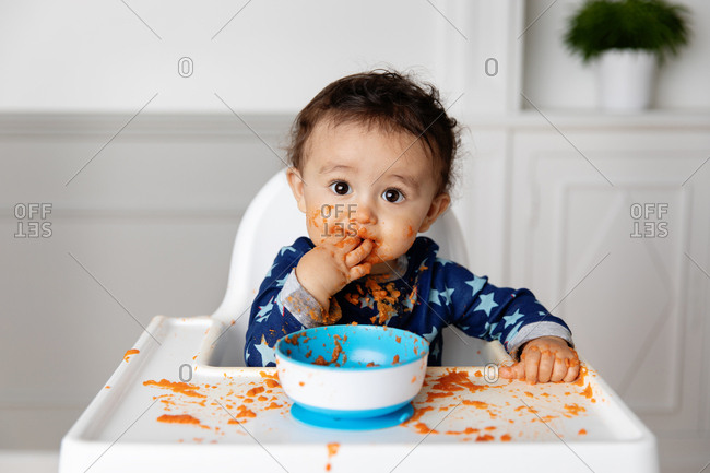 Toddler making a mess with a bowl of pasta sauce
