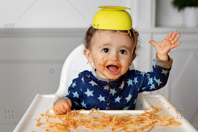 Toddler in high chair with a bowl of spaghetti on his head