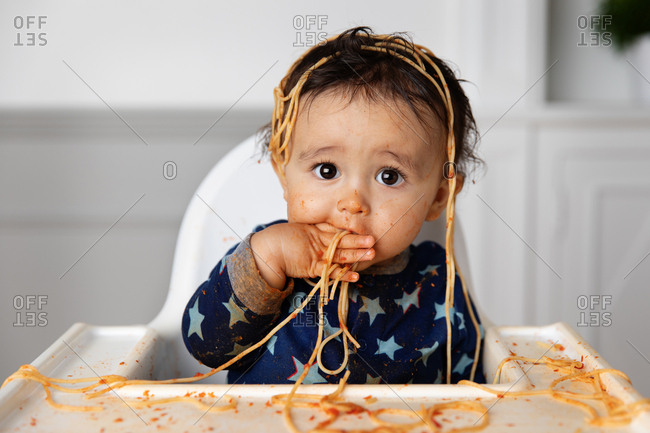Toddler in high chair making a mess while eating spaghetti