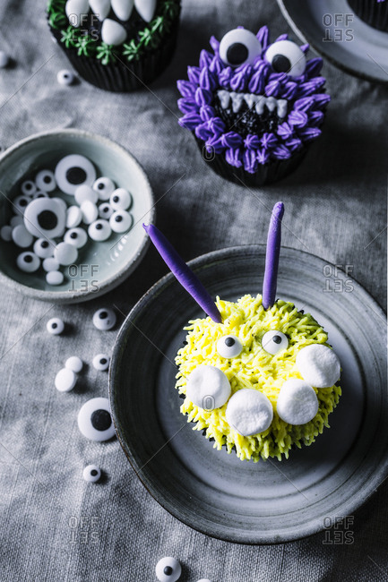 Overhead view of yellow and purple monster themed cupcakes