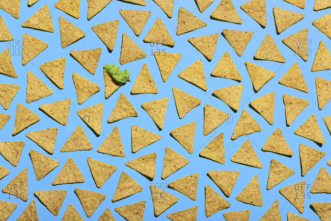 High Angle View of Tortilla Chips on Blue Background, One Chip has Guacamole
