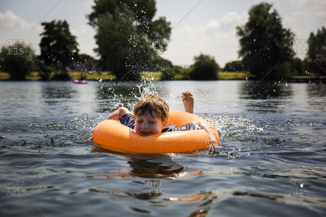 Boy swimming in a lake with a swim ring