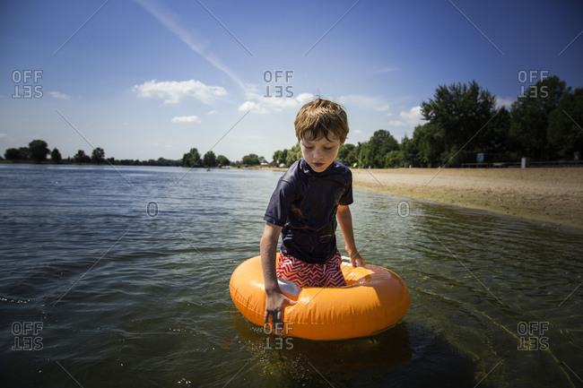 Young boy standing in an innertube in shallow water