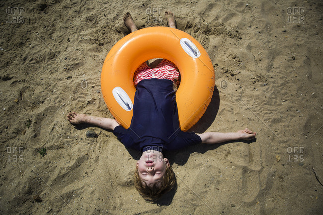 Overhead view of boy sleeping in an innertube