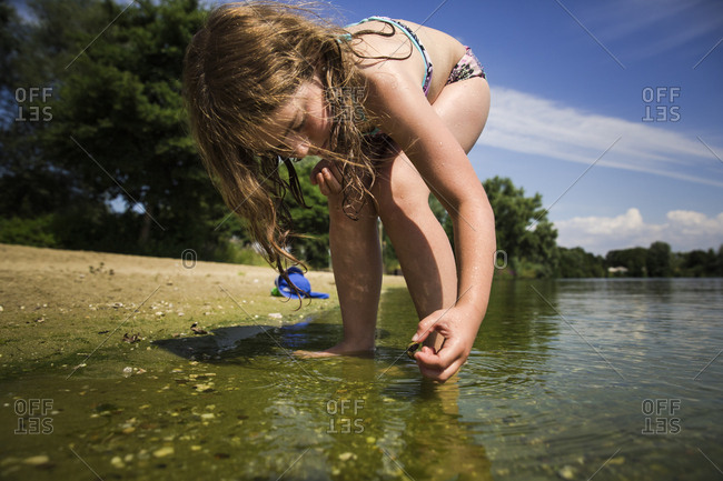 Girl picking up snails from the water