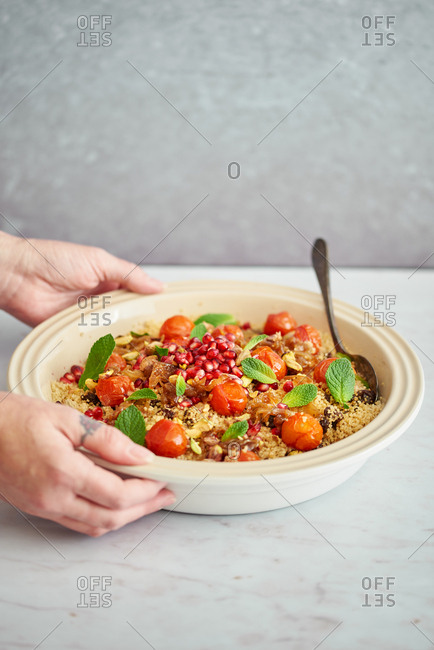 Woman serving bowl of Moroccan couscous pilaf