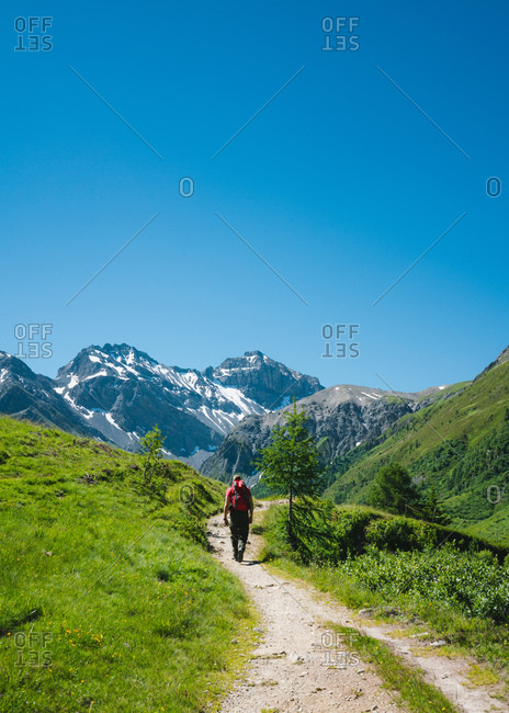 Man hiking in the Swiss Alps under clear blue sky