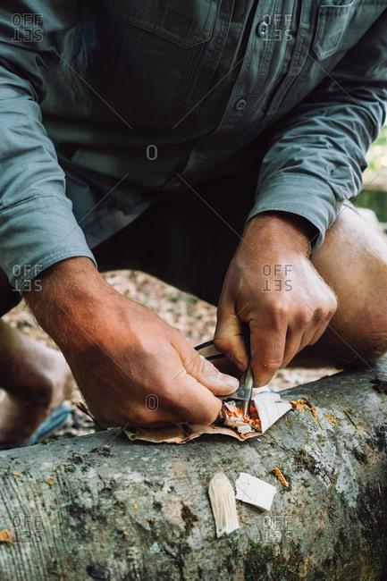 Man lighting fire in forest - Bushcraft Skills