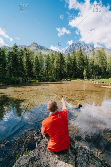 Man sitting above clear Alpine lake and idyllic forest, Switzerland