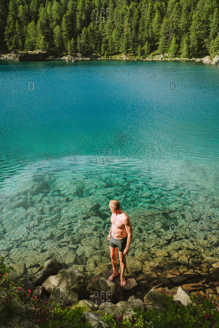 Man swimming in beautiful turquoise Alpine lake, Switzerland