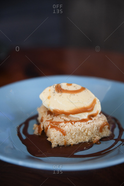 Cake topped ice cream and syrup