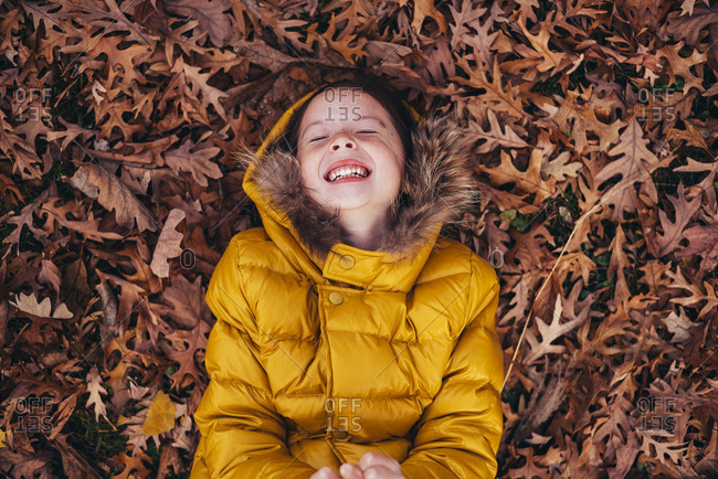 Overhead portrait of young girl playing in fall leaves