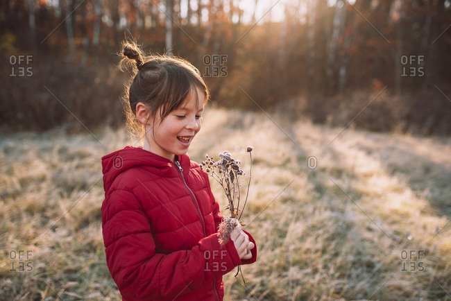 Young girl exploring nature in a frost covered meadow
