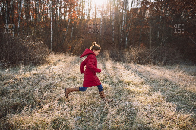Young girl running in a frost covered meadow