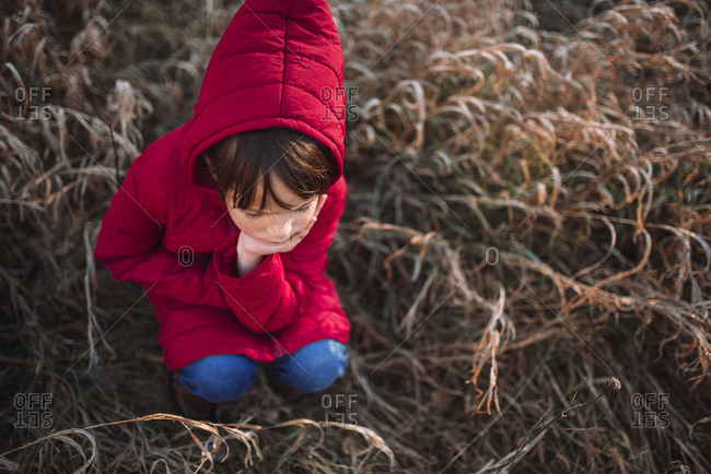 Overhead view of young girl sitting in dried grass