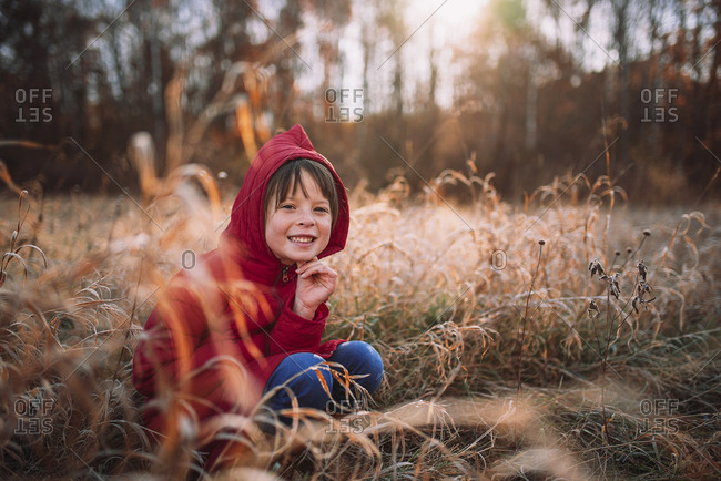 Young girl smiling and sitting in the forest