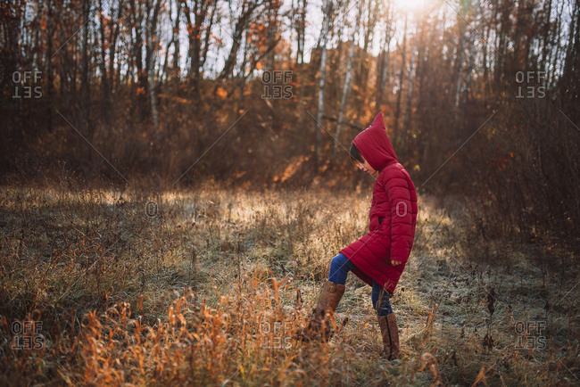 Young girl hiking in a frost covered meadow