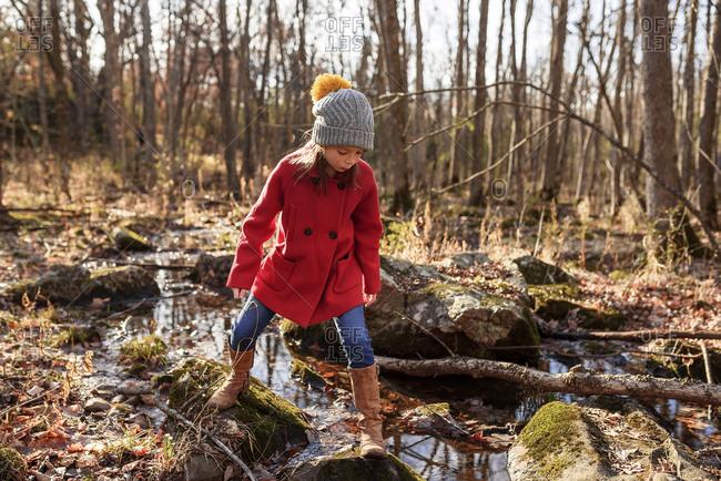 Young girl climbing along a small creek