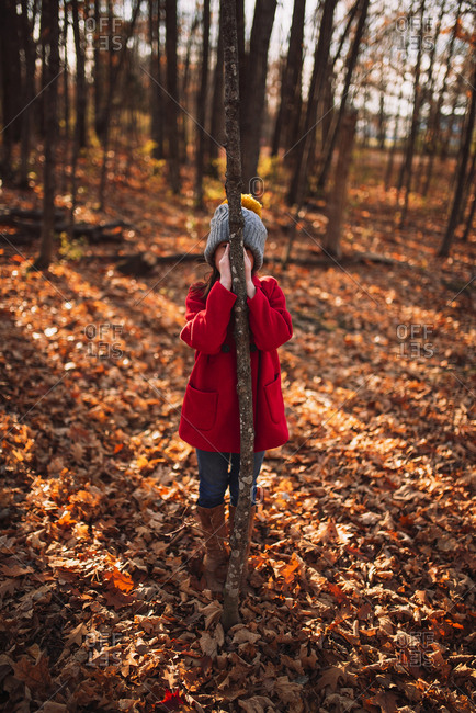 Young girl hiding behind a tree in autumn
