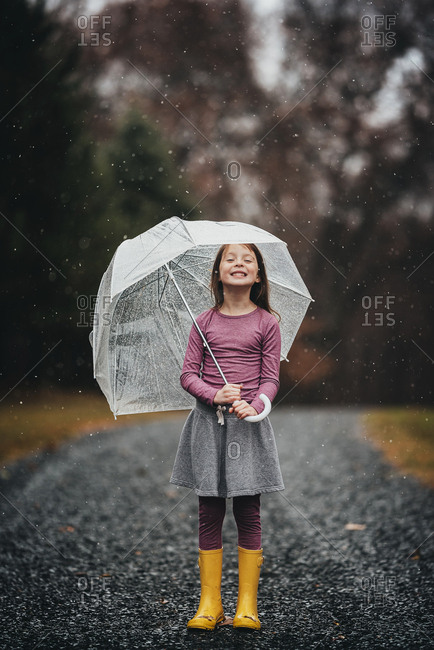 Young girl with an umbrella playing in the falling rain or snow