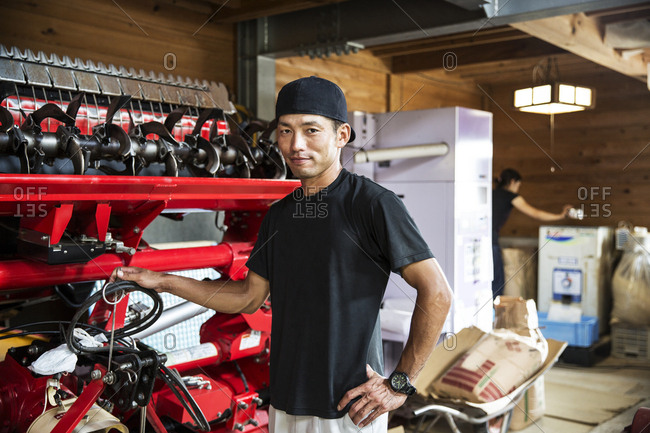 Japanese farmer wearing black cap standing next to agricultural machine, smiling at camera.