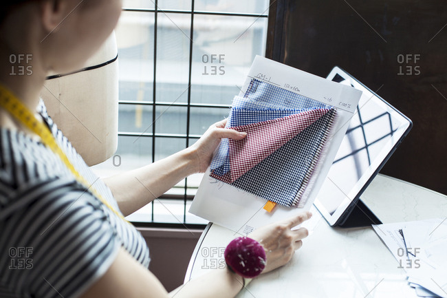 Japanese female fashion designer working in her studio, sitting at table, looking at fabric samples.