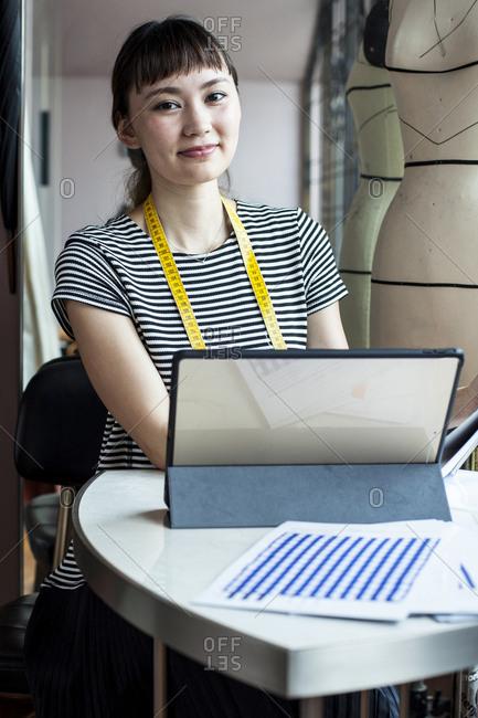 Japanese female fashion designer working in her studio, smiling at camera.