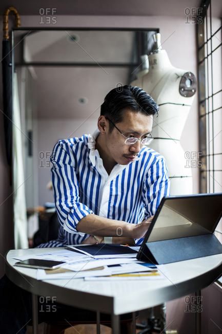 Japanese male fashion designer working in his studio, sitting at table, looking at digital tablet.