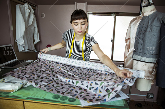 Japanese female fashion designer working in her studio, measuring fabric.