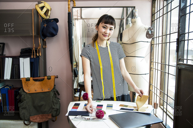 Japanese female fashion designer working in her studio, smiling at camera.