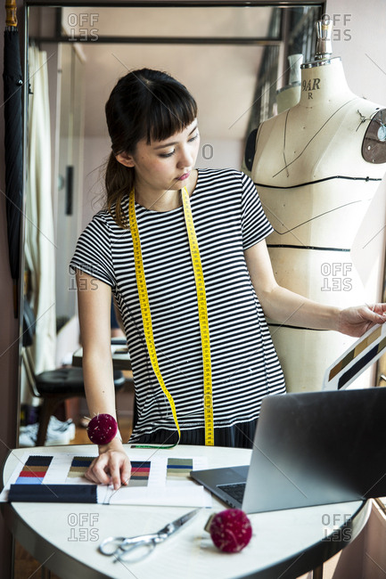 Japanese female fashion designer standing at desk, working in her studio.