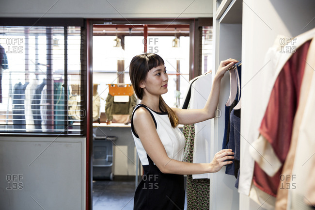 Japanese saleswoman standing in clothing store, hanging blue waistcoats on rail.