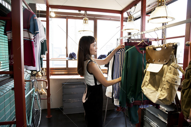 Japanese saleswoman standing in clothing store, arranging clothes on a rail.