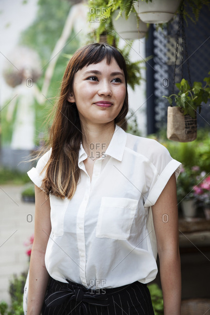 Smiling Japanese woman with long brown hair wearing white short-sleeved blouse standing in a street.