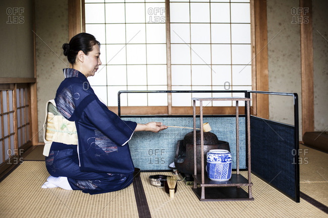 Japanese woman wearing traditional bright blue kimono with cream coloured obi kneeling on floor, using a  Hishaku, a bamboo ladle, during a tea ceremony.