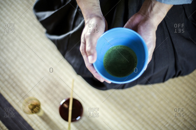 High angle close up of Japanese man wearing traditional kimono kneeling on floor holding blue bowl with Matcha tea during tea ceremony.