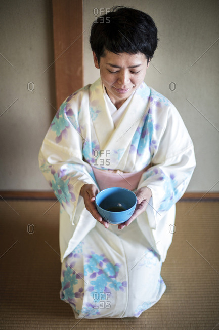 Japanese woman wearing traditional white kimono with blue floral pattern kneeling on floor during tea ceremony, holding blue tea bowl.