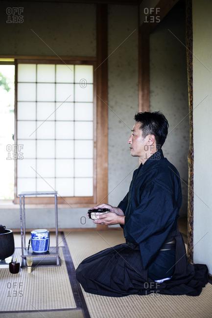 Japanese man wearing traditional kimono kneeling on floor, holding tea bowl, during tea ceremony.