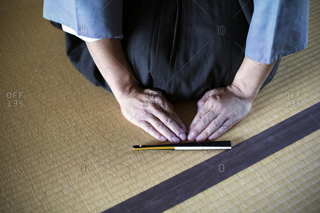 High angle close up of Japanese man kneeling on tatami mat in front of Sensu fan during a tea ceremony, used as a greeting.